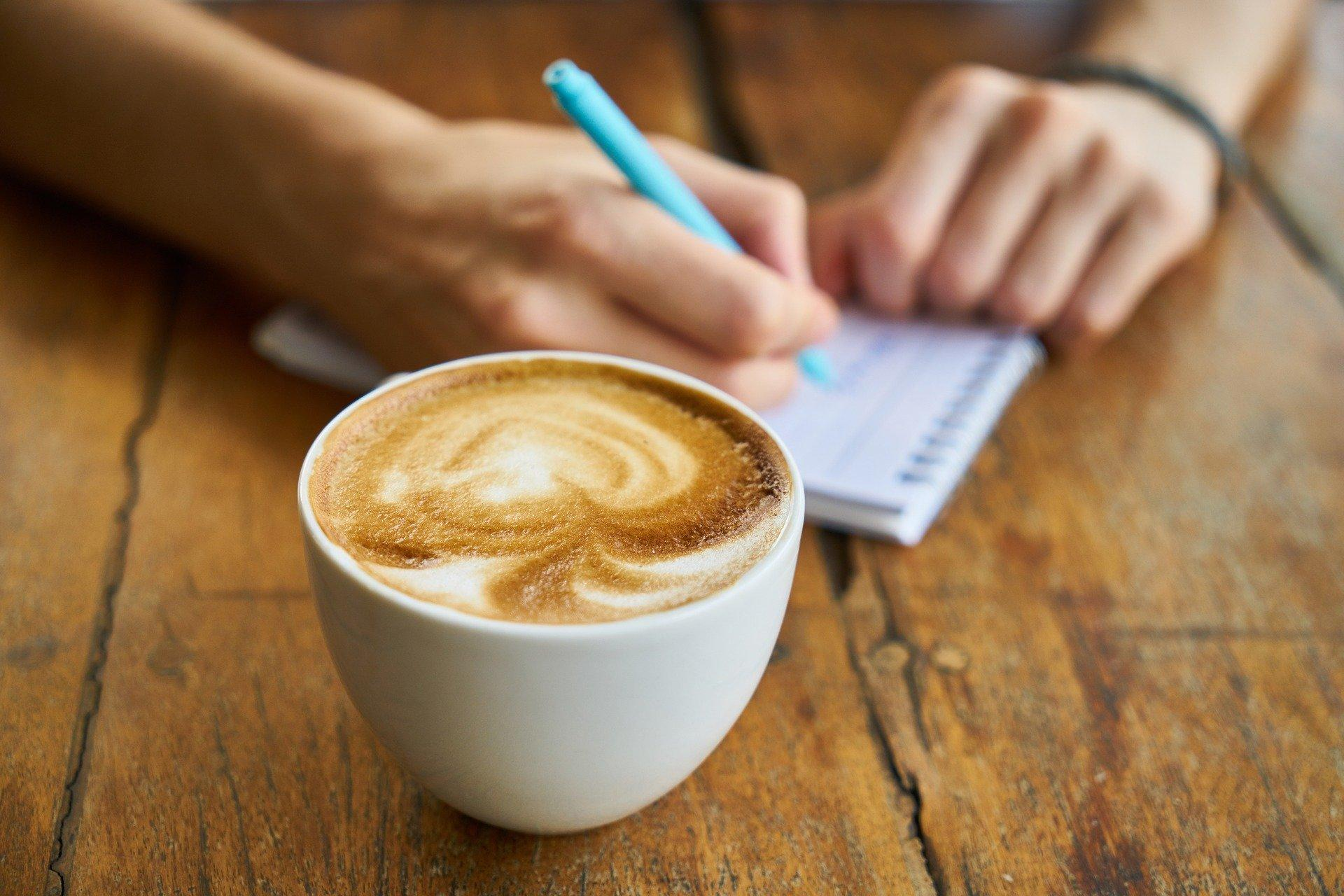 Hotel owner writing a list and having a coffee
